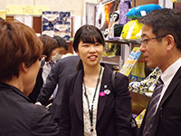Designer Ms. Ito wearing our embroidered brooch, talking with customer with smile.