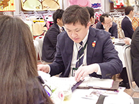 Mr. Miyaguchi Manager in a meeting with spreading information sheets.