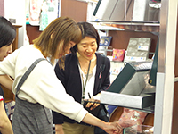 The customer picking up our products in her hand. Designer Ms. Moriya explain product so that she can understand.