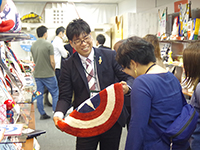 Mr. Katayama pick up the product and explaining to the customer.